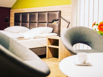Eskapada - pokój 7-widok na stolik z łóżkiem w tle