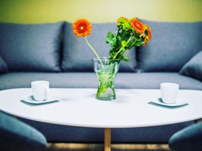Eskapada-pokój 7 -detal z kwiatami i kanapą w tle