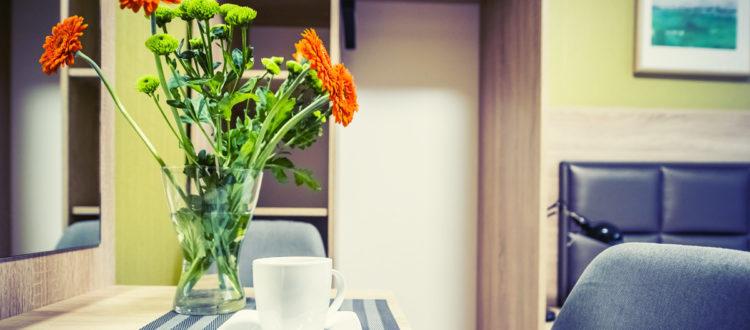 Eskapada -pokój 6-detal z kwiatami i szafą w tle
