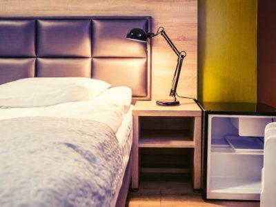 Eskapada - pokój 6 -łóżko i lodówka w świetle lampek nocnych