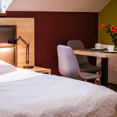 Eskapada - pokój 5 -widok na łóżko i stolik w tle
